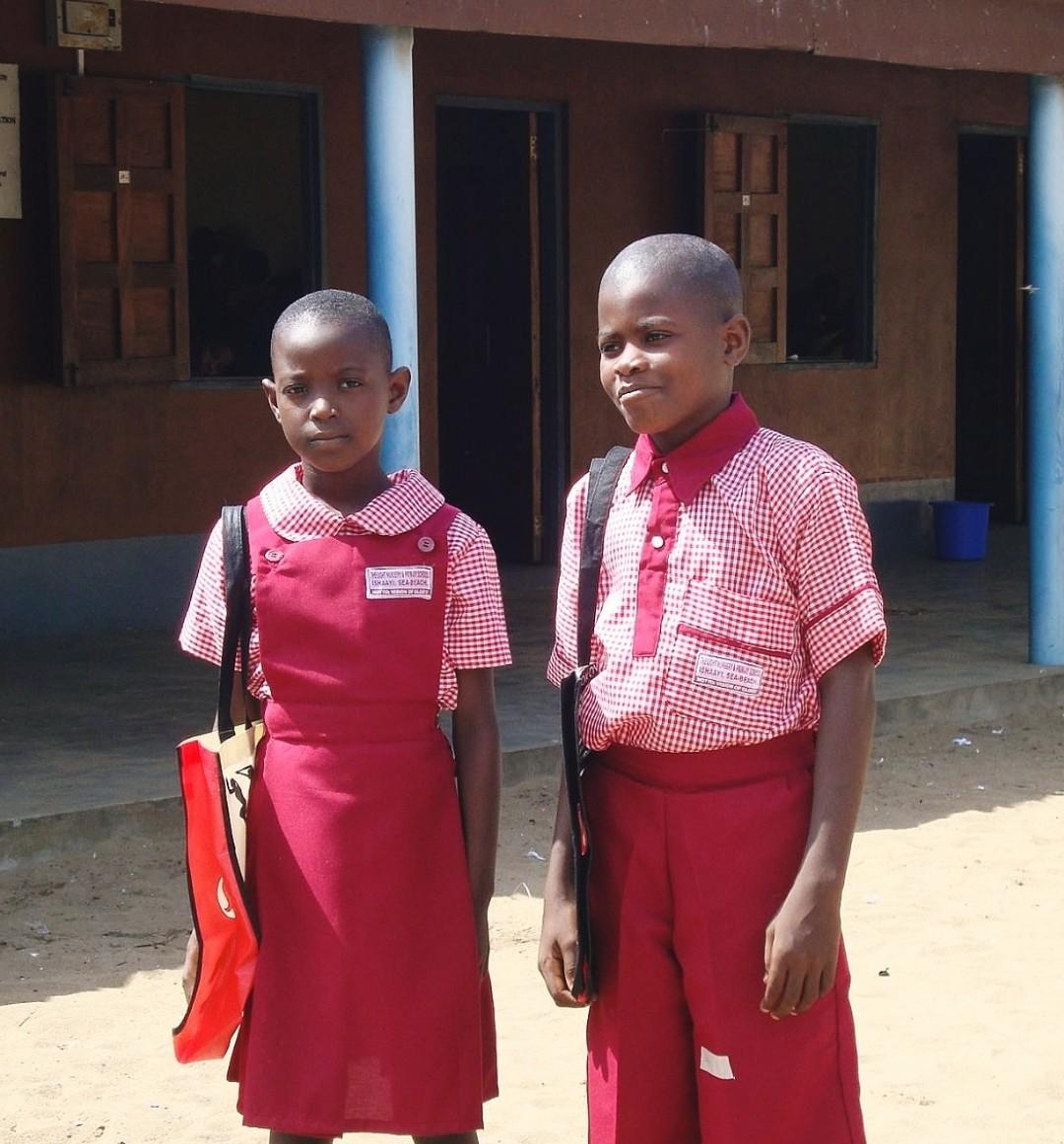 Two children model their new school uniforms.