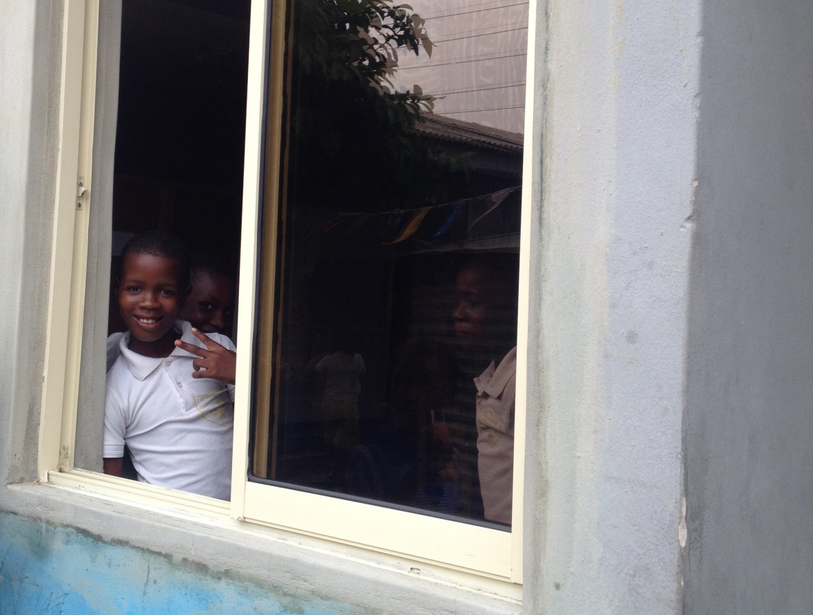 After: a student poses for the camera through an open classroom window.
